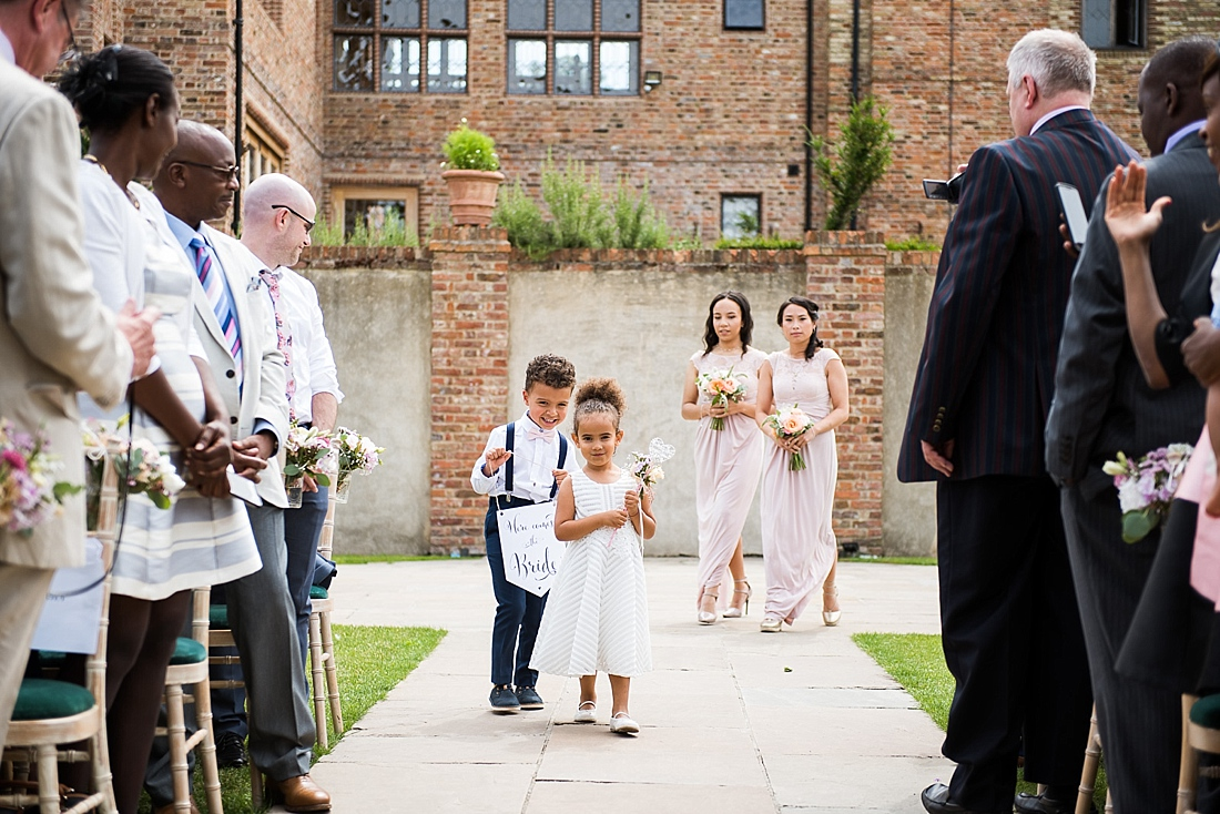 Cute flower girl with page boy then Asos bridesmaids walk outdoor aisle