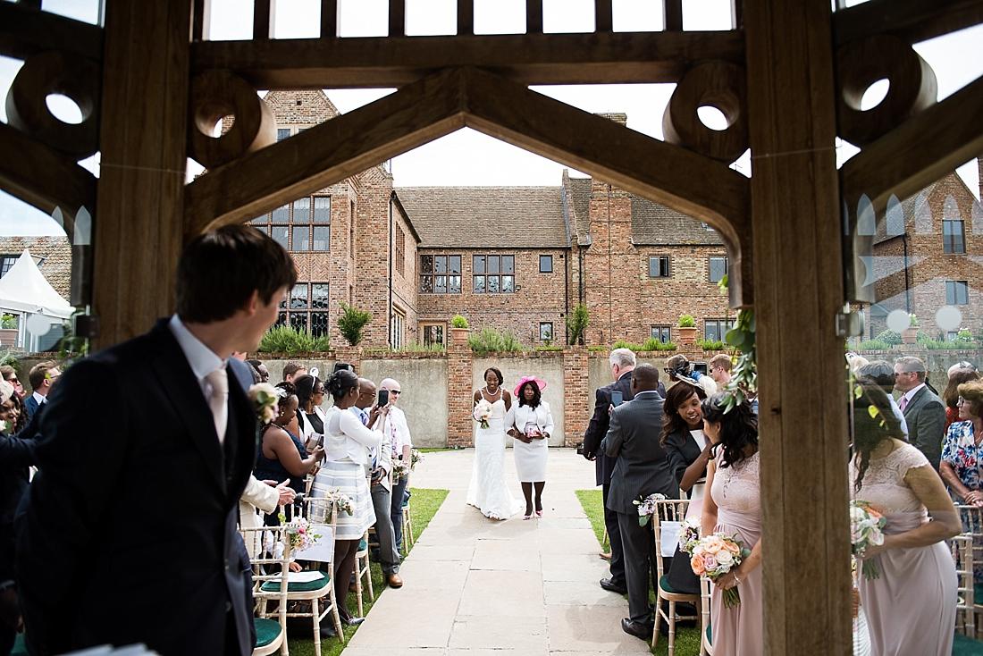 Elegant mother walking bride down aisle outdoor wedding ceremony