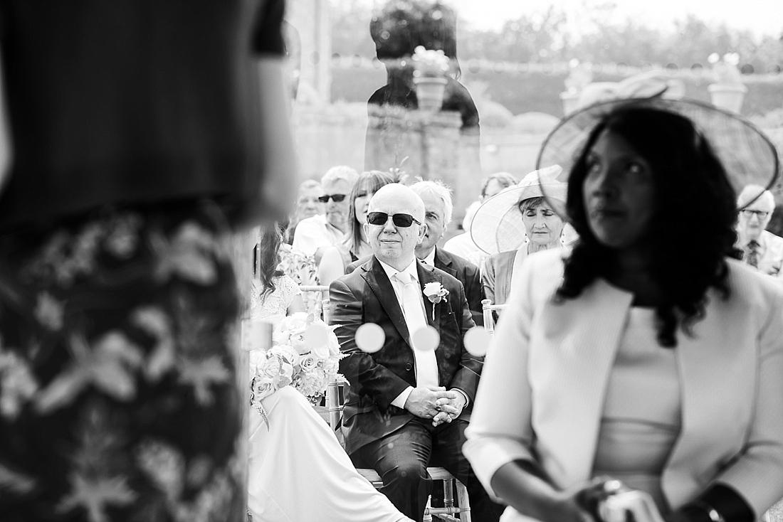 Wedding guests watch summer outdoor wedding ceremony