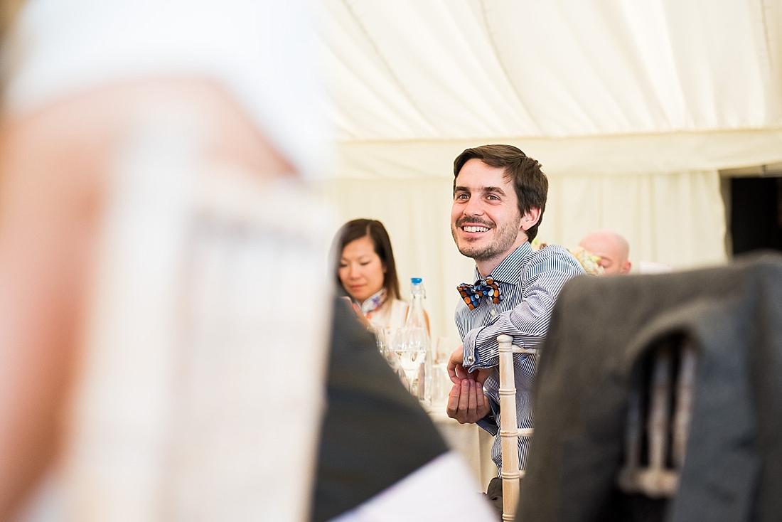 Smiling wedding guest listens during wedding speech