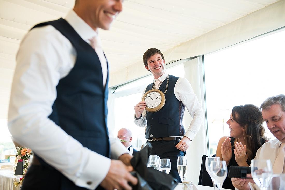 Smiling groom with ticking clock around neck