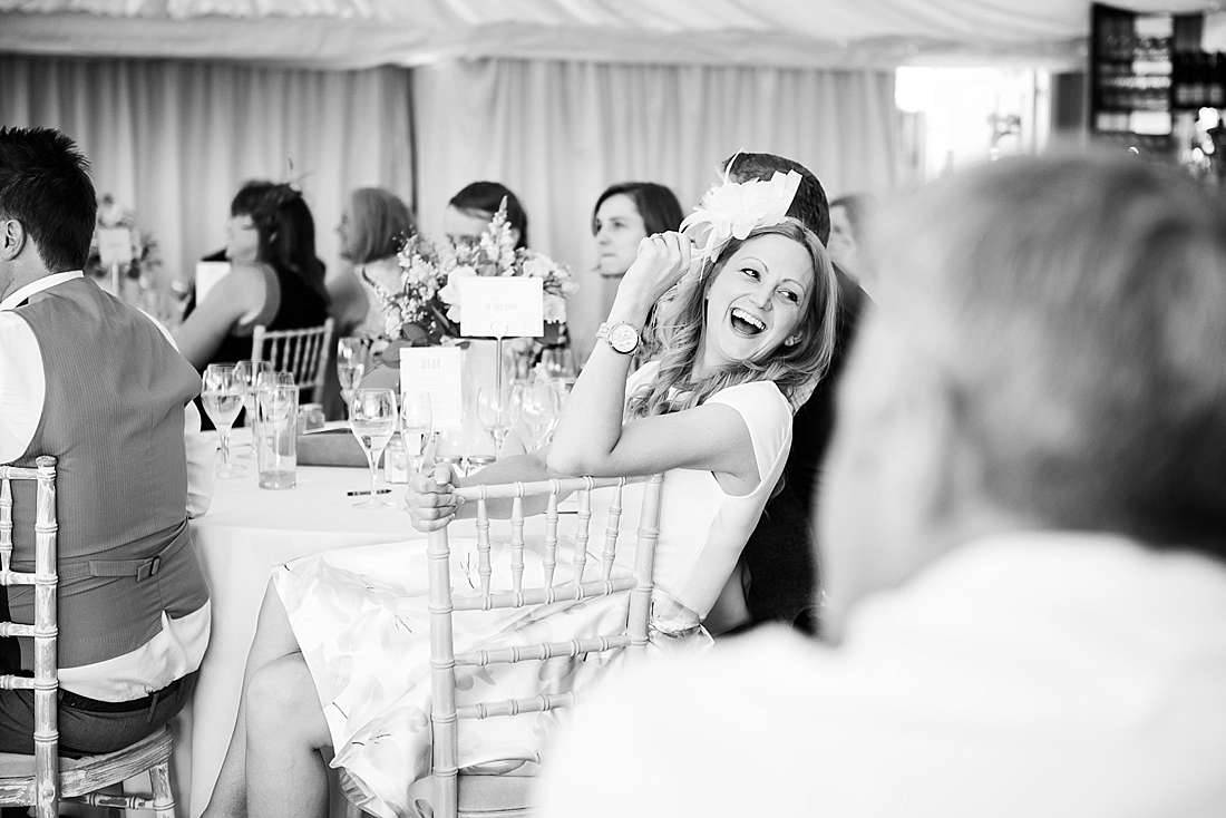 Wedding guest laughing during wedding speech