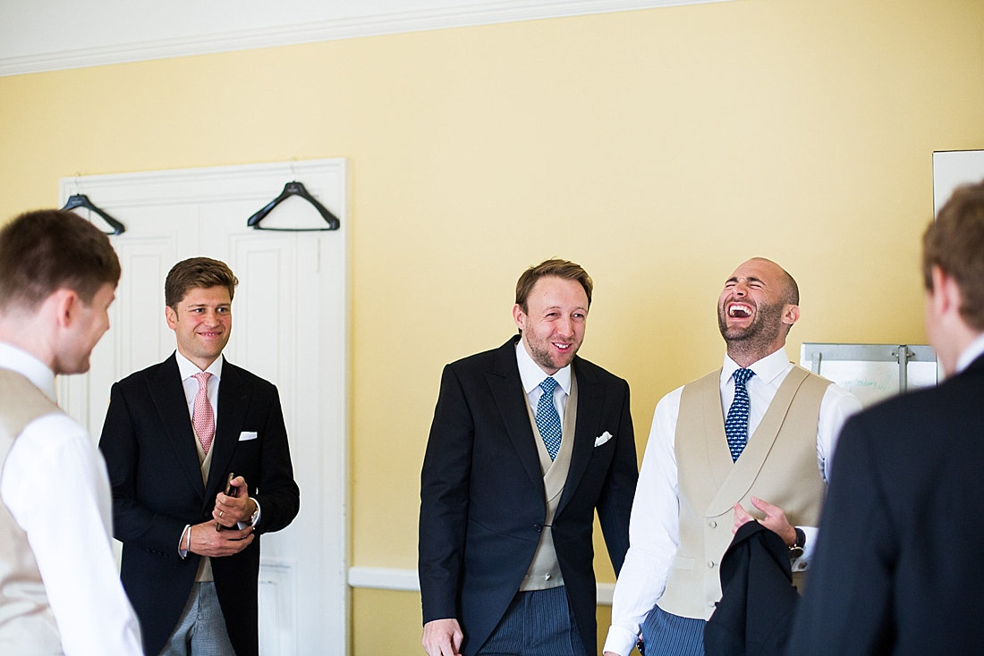 Laughing groom with groomsmen wearing Neal & Palmer suits