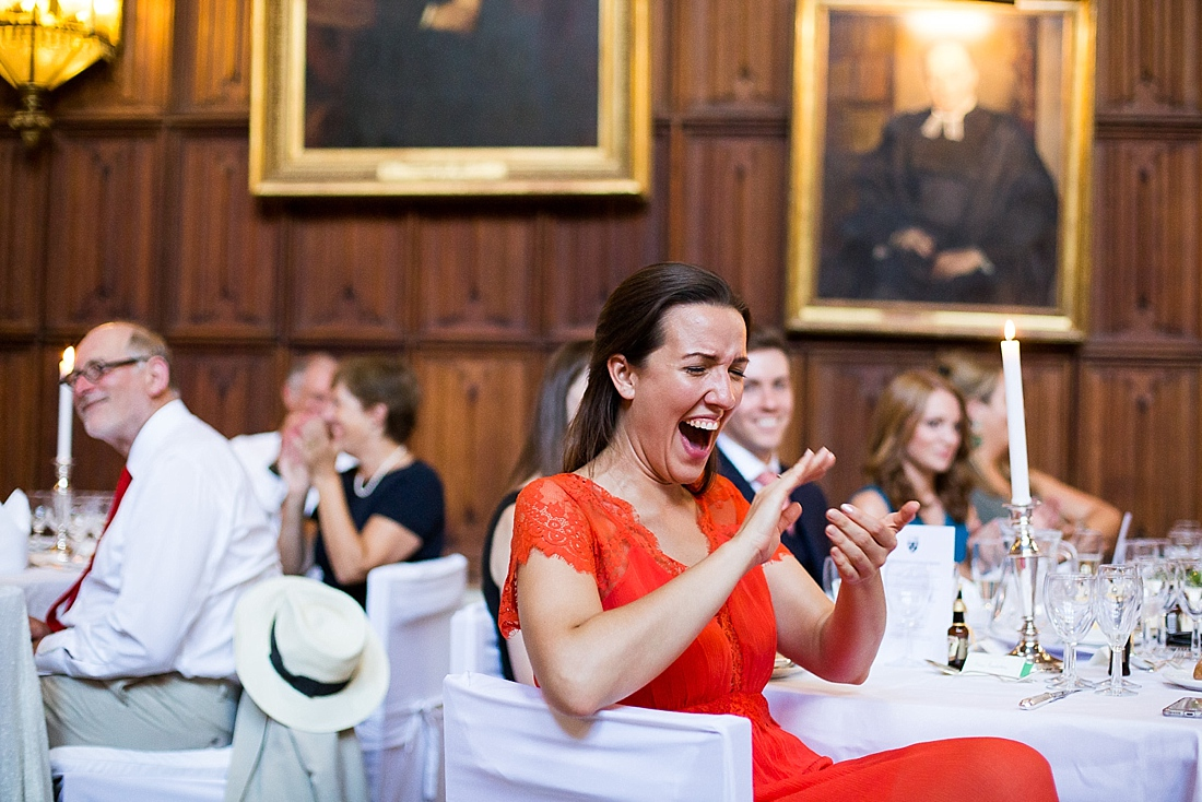 Wedding guest laughing wearing red dress