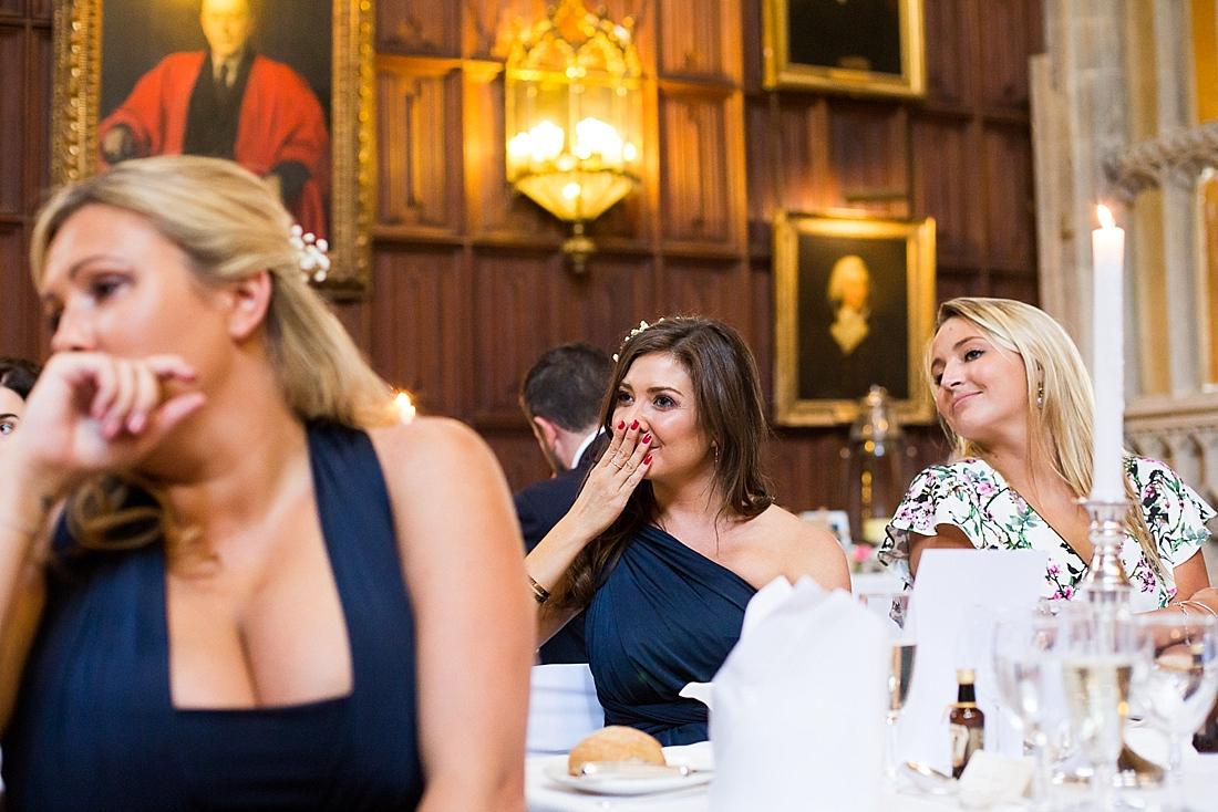 Emotional wedding guests listen during speech