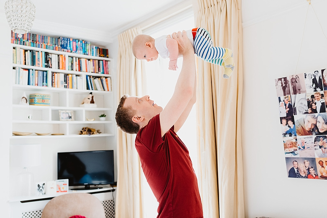 Dad flying baby in air wearing stripy trousers London family photography