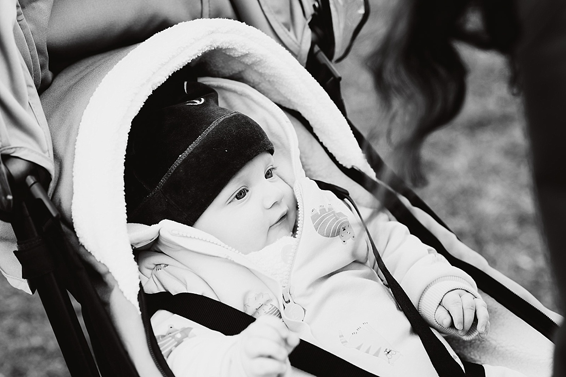 Relaxed photography style baby seated in pram outside London