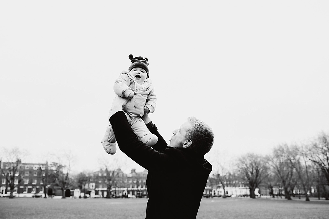 Natural wedding photography Father holding baby high in sky London