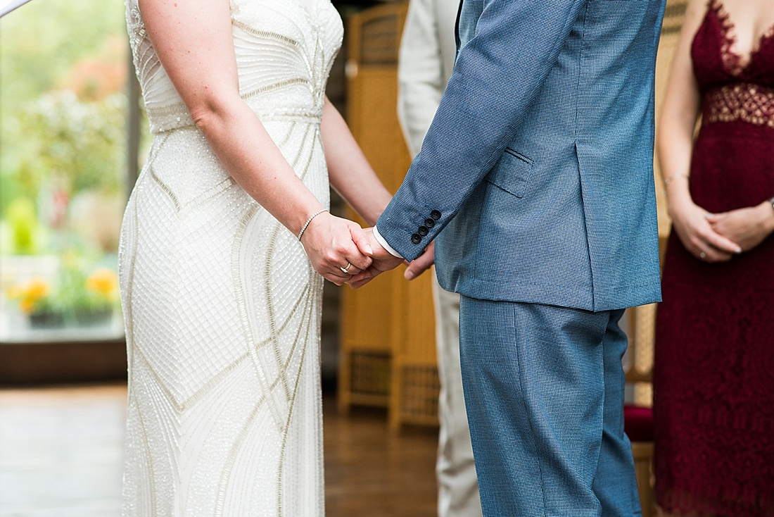 Bride with groom hold hands during wedding ceremony