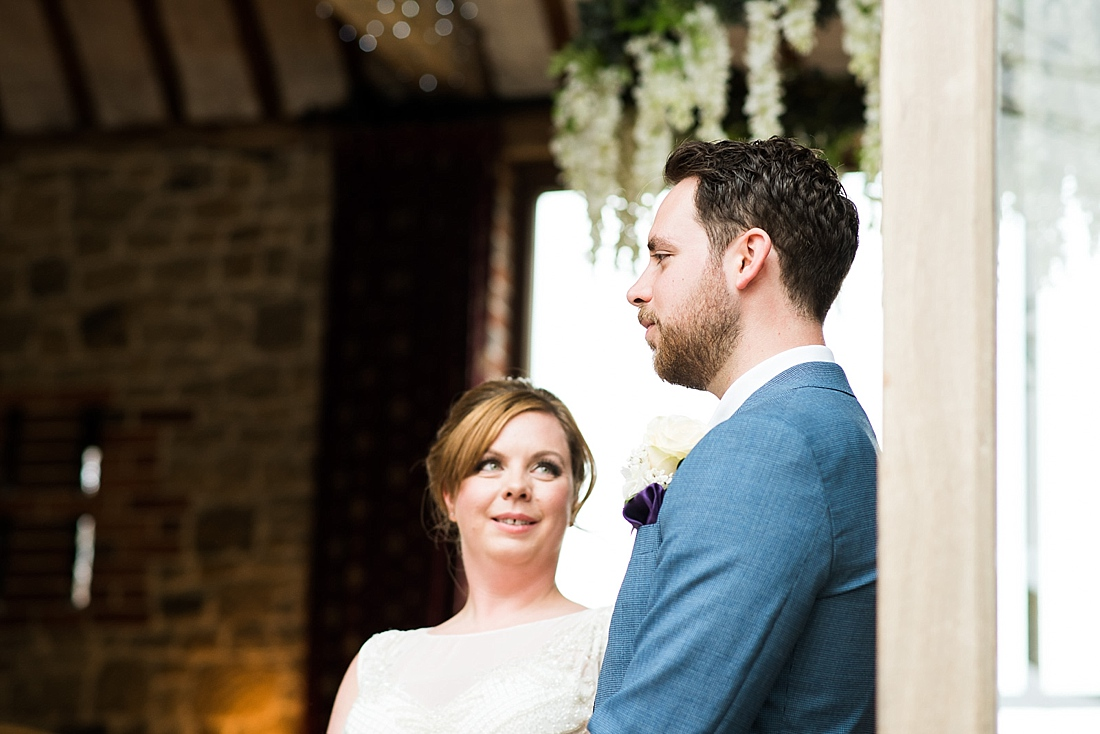 Stylish bride looks at groom saying vows