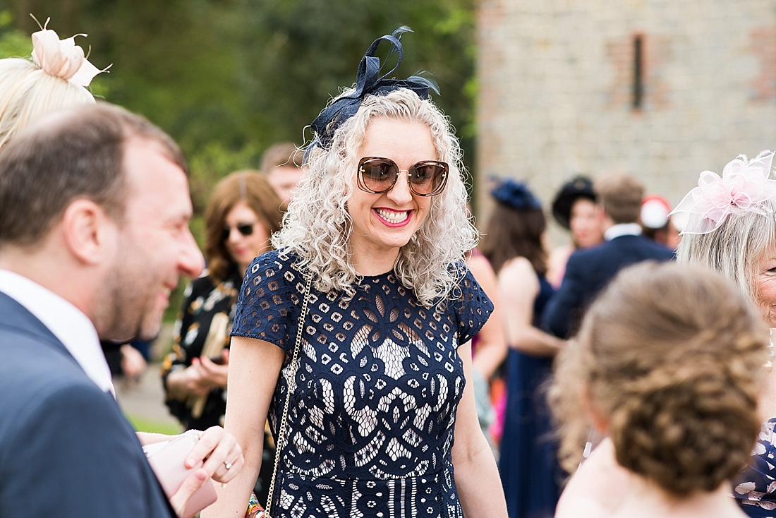 Smiling wedding guest wearing fascinator with lace dress