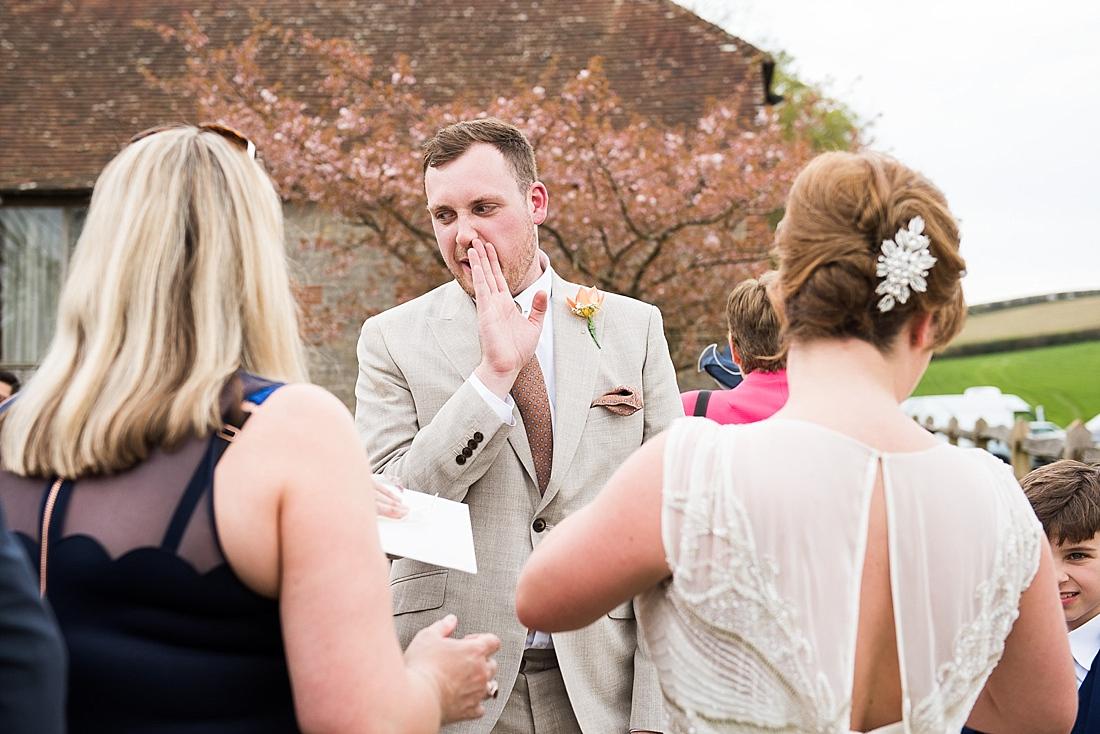 Groomsmen whispering sunny outdoor wedding