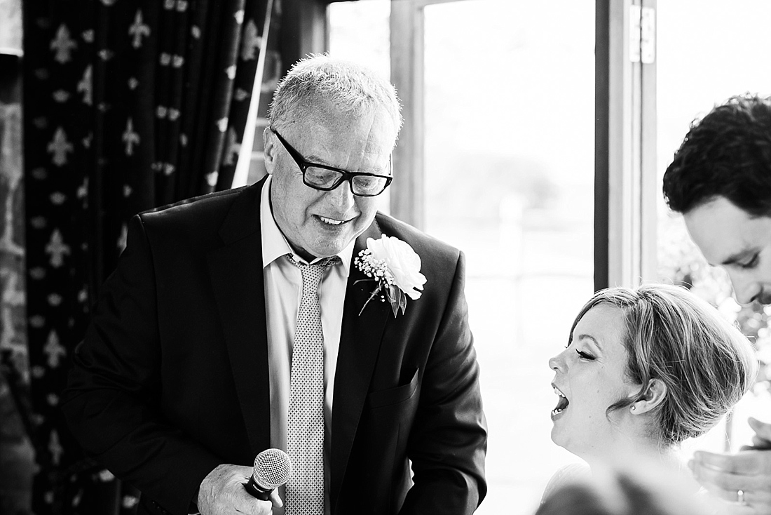 Father with daughter laugh during wedding speech