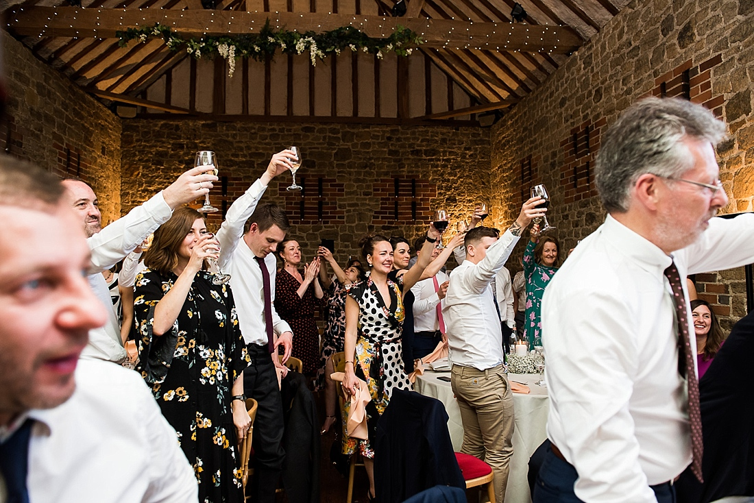Wedding guests stand to toast bride and groom
