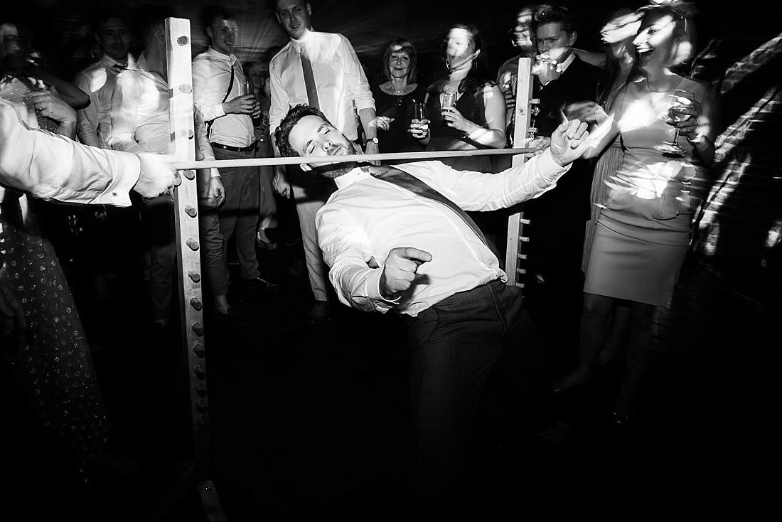 Guy performing limbo at wedding