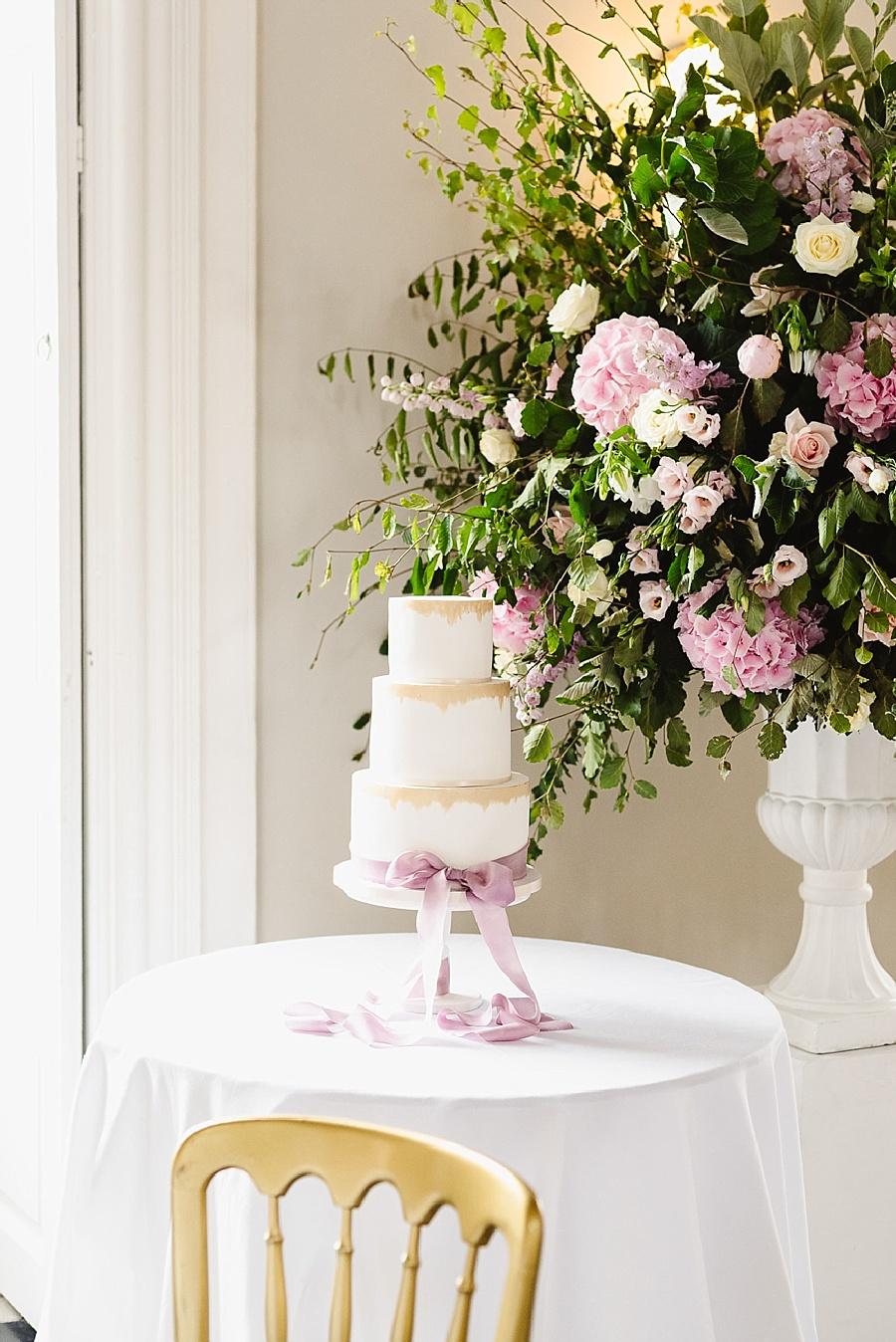 Elegant wedding cake with pink ribbon